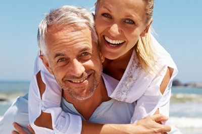 Couple with golden tans embracing and smiling outdoors
