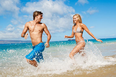 Couple running on beach with natural-looking golden tans